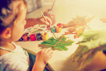 Cute little girl drawing with paint autumn leaves at home