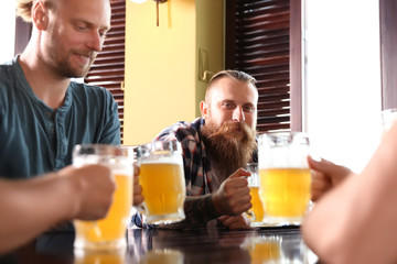 Friends drinking beer at table in pub