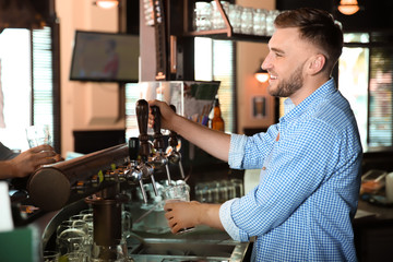 Bartender working at beer tap in pub