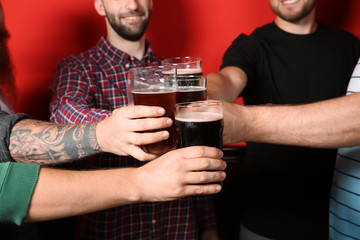 Group of friends clinking glasses with beer on color background