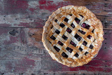 Baked cherry pie on rustic wood table flat lay