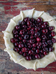 Uncovered Pie shell pastry dough with ripe cherries on rustic wood table flat lay