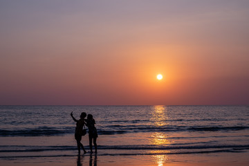 Couple taking selfie during sunset on the beach