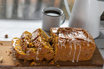 Pumpkin bread loaf in pan on rustic white painted table flat lay