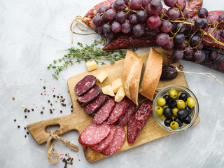 Different sausages with cheese, grapes and olive. Sliced Salami in rustic style