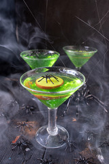 Halloween bright green dessert topped with apple slice with spooky smoke trails and black spiders and spider webs