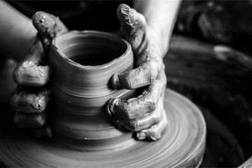 Hands of potter making clay pot, closeup photo