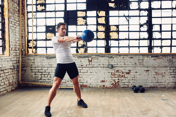 Caucasian Man Performs a Kettle Bell Swing for a Work Out