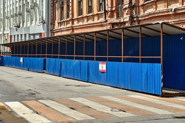 pedestrian crossing with a canopy of corrugated metal blue sheet metal and dervish flooring along the construction site with a dangerous zone