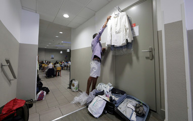 "A homeless man packs his belongings in the ""Abbe Pierre"" night shelter for the homeless in Nice"