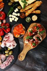 Italian antipasti wine snacks set. Cheese variety, Mediterranean olives, pickles, Prosciutto di Parma, tomatoes, artichokes.