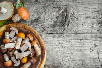 Fresh mixed forest mushrooms on the wooden black table, top view. Copy space