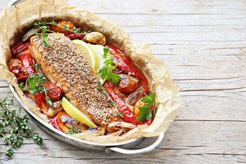 Fish and vegetables. Oven baked sesame salmon  with roasted vegetables, lemon and herbs.  Selective focus