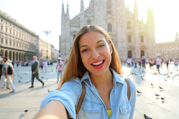 Happy young woman take selfie photo in front of Milan Cathedral. Self portrait of beautiful girl in Milan, Italy.