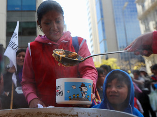 People receive a free meal at a soup kitchens set up on a street during a demonstration against the government's economic measures in Buenos Aires