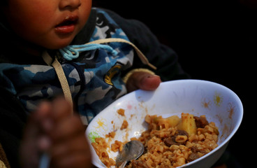 A child eats a free meal at a soup kitchen set up on a street during a demonstration against the government's economic measures in Buenos Aires