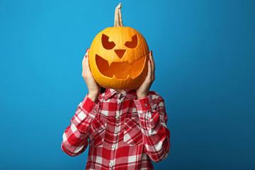 Female hands holding halloween pumpkin on blue background