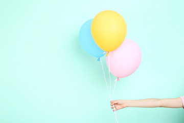 Female hand holding colorful balloons on mint background