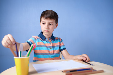 Caucasian boy spending time drawing with colorful pencils at home.
