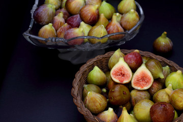 Ripe figs in a wicker basket on dark background