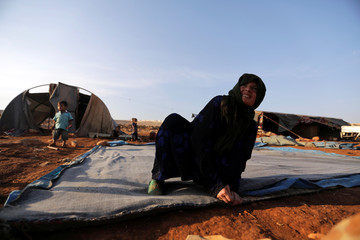 A newly displaced Syrian woman prepares a tent near a refugee camp in Atimah village, Idlib province