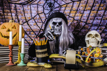 man in Grimm reaper robe skull mask and skeleton hands pointing at camera with pencil surrounded by human skull jack o lantern burning candles large yellow snake black spider and web