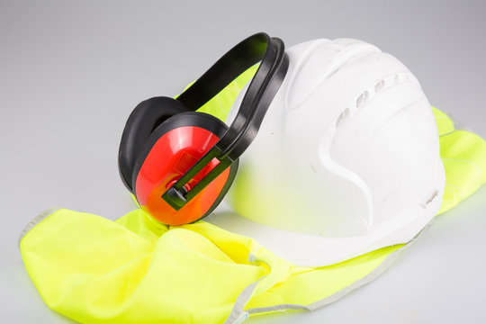 white helmet ear muffs placed on yellow vest with Reflective on white background in safety work concept