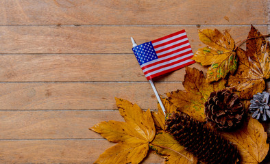 little flag of USA with maple leaves on wooden table. Above view