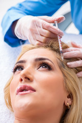 Plastic surgeon preparing for operation on woman hair