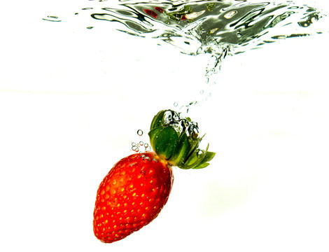 Strawberry dropped into liquid for artistic shot