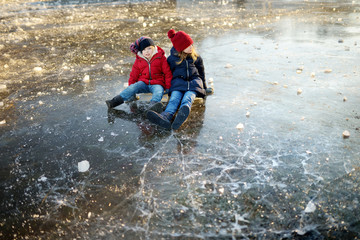Two happy sisters playing with ice blocks by frozen river during an ice break. Children having fun in winter.