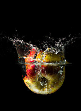 An apple dropped into liquid creating a beautiful splash