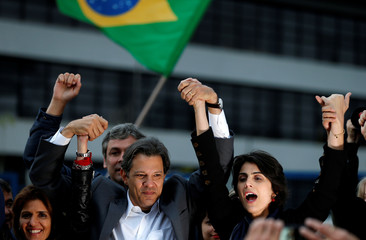 Workers Party Presidential candidate Fernando Haddad, raises hands with his vice presidential candidate Manuela d'Avila in front of the Federal Police headquarters, where Brazilian former President Luiz Inacio Lula da Silva is imprisoned, in Curitiba