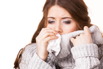 Sick freezing woman sneezing in tissue