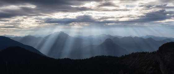 Striking panoramic landscape view of the Canadian mountain landscape with sunrays during a cloudy morning. Taken near Vancouver, BC, Canada.