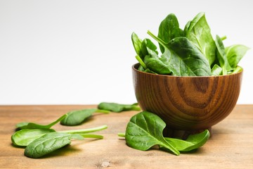 Young Spinach Leaves On Wooden Table And More In Bowl