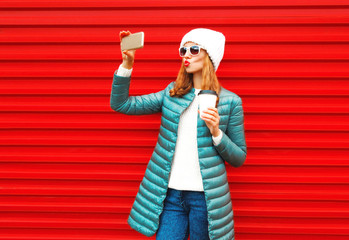 Fashion pretty woman takes a picture self portrait on a smartphone on red background