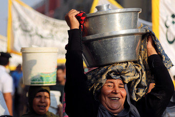 An Egyptian woman carries cooking pots to distribute free food to Muslims during the celebratation of the Islamic New Year outside the Al-Hussein mosque in old Cairo