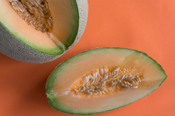 melon wedge on orange background. Sweet, juicy fruit, ideal snack for healthy dieting.