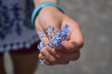 Girl holding light blue color flowers