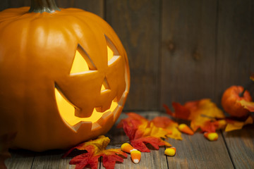An angled jack-o-lantern with fall maple leaves and candy corns on a wooden background