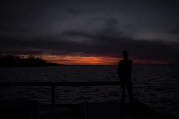 Mysterious silhouette man on the peer at sunset