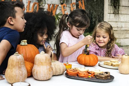 Young kids carving Halloween jack-o'-lanterns