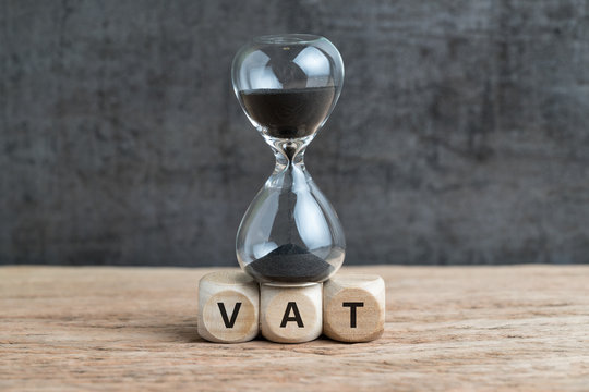 Time countdown for VAT increase deadline concept, hourglass or sandglass on cube wooden block with alphabets VAT, Value Added Tax on wood table with dark black loft cement wall