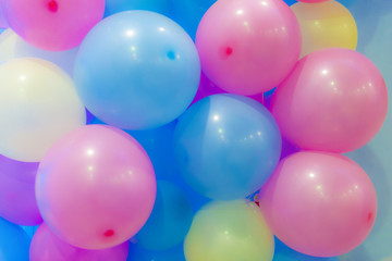 Many colorful balloons decorated wall as background.