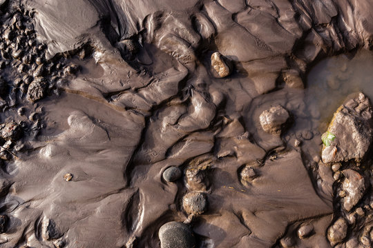 Glacial riverbank shore with wet black silt sand mud