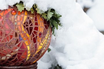 Cold snow day with close-up of gold, red, yellow, orange, bright multicolored stained glass mosaic garden art ball in winter