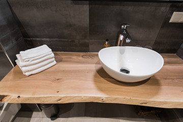 Modern interior of the bathroom. The washbasin is made of white massive shell on the table of wood. Minimalism and simplicity in a bright grey functional interior. Top view Fototapete