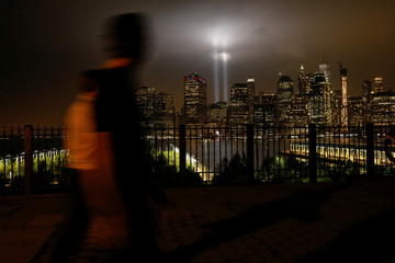 A man looks at the Tribute in Light installation as it illuminates over lower Manhattan as seen from the borough of Brooklyn, marking the 17th anniversary of the 9/11 attacks in New York