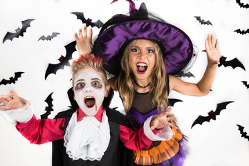 Halloween kids, Happy scary girl and boy dressed up in halloween costumes of witch, sorcerer and vampire, Dracula for pumpkin patch and halloween party